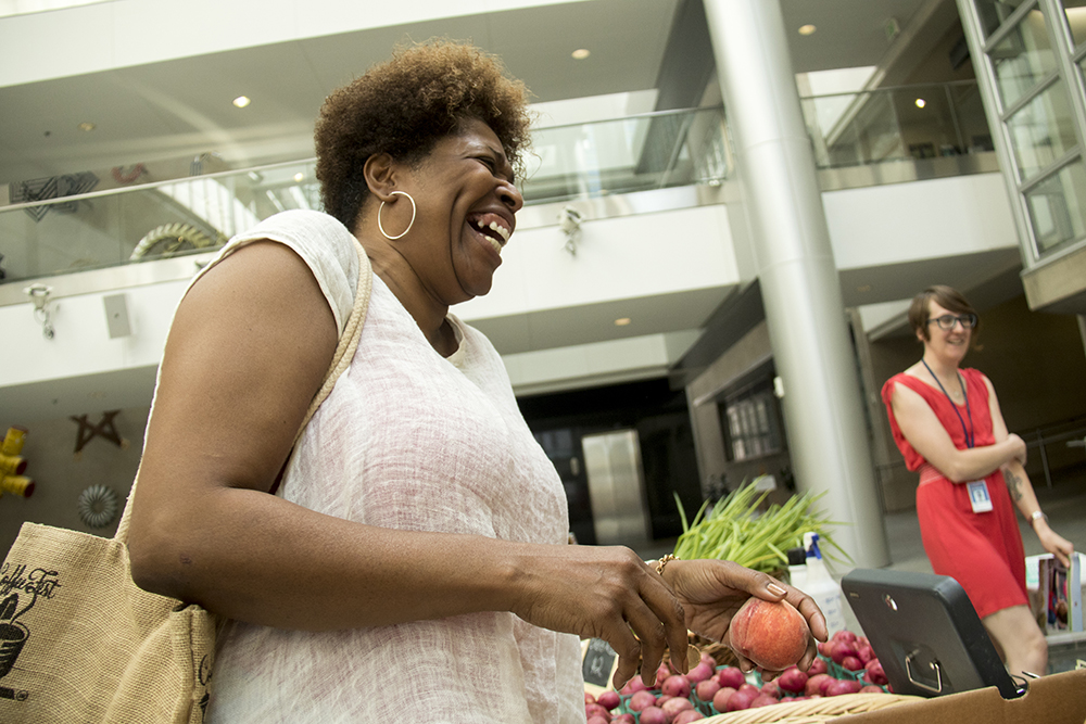 Victoria Lindsay is stoked for peach cobbler season as she selects ingredients for her master plan. The Denver Botanic Gardens' farmer's market is set up inside the Wellington Webb Building downtown. July 19, 2017. (Kevin J. Beaty/Denverite)  denver; colorado; denverite; kevinjbeaty; farmers market; food; produce; farming; denver botanic gardens chatfield farm; wellington webb building; grocery;