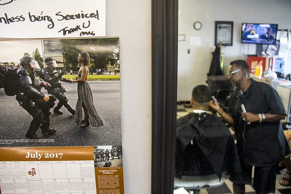Chuck Sagere's shop, Montbello Barbers, is adorned with multiple images and symbols of civil rights struggles. July 25, 2017. (Kevin J. Beaty/Denverite)  denver; colorado; denverite; barber shop; montbello; montbello barbers; community; kevinjbeaty;