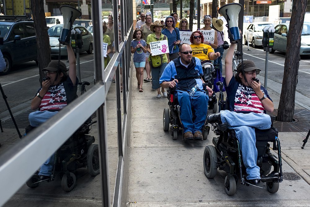 Jordan Sibayan leads the crowd around the building that contains Sen. Cory Gardner's office. An ADAPT protest against yet another healthcare bill in Washington that could strip Medicaid coverage. Skyline Park, July 27, 2017. (Kevin J. Beaty/Denverite)  adapt; healthcare; denver; colorado; denverite; skyline park; medicaid; kevinjbeaty;