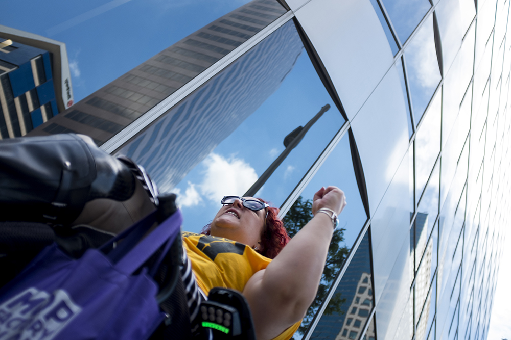 """Sarah Nelson yells, """"Kill the bill! Don't kill us!"""" An ADAPT protest against yet another healthcare bill in Washington that could strip Medicaid coverage. Skyline Park, July 27, 2017. (Kevin J. Beaty/Denverite)  adapt; healthcare; denver; colorado; denverite; skyline park; medicaid; kevinjbeaty;"""