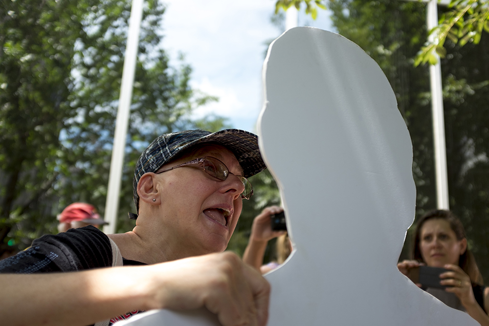 ADAPT protester Dawn Howard voices her concerns to a cut-out Cory Gardner. An ADAPT protest against yet another healthcare bill in Washington that could strip Medicaid coverage. Skyline Park, July 27, 2017. (Kevin J. Beaty/Denverite)  adapt; healthcare; denver; colorado; denverite; skyline park; medicaid; kevinjbeaty;
