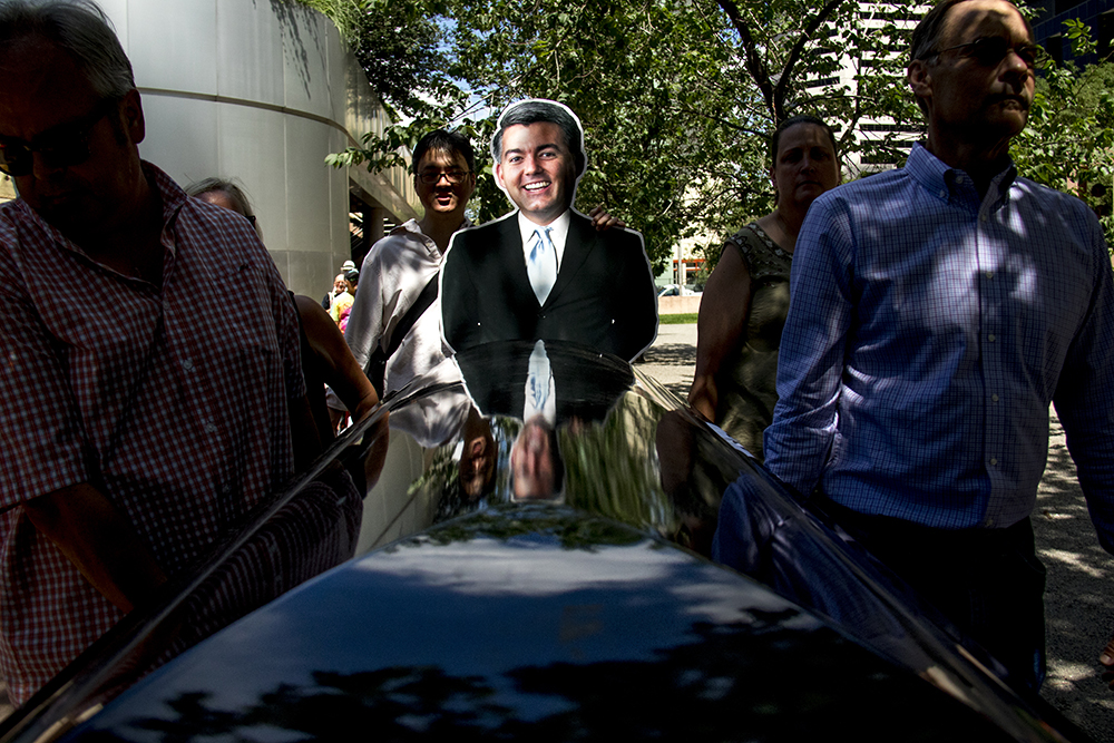 A cutout of Cory Gardner is reflected in a casket as it circles the building containing his office. An ADAPT protest against yet another healthcare bill in Washington that could strip Medicaid coverage. Skyline Park, July 27, 2017. (Kevin J. Beaty/Denverite)  adapt; healthcare; denver; colorado; denverite; skyline park; medicaid; kevinjbeaty;