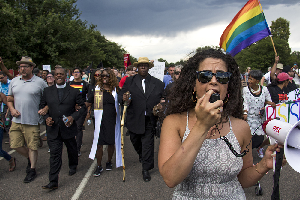 Hanna Khavafipour leads the march out of City Park with a bullhorn. A rally in response to white supremacist protests in Charlottesville, VA, Aug. 13, 2017. (Kevin J. Beaty/Denverite)  protest; charlottesville; rally; denver; colorado; kevinjbeaty; denverite; city park