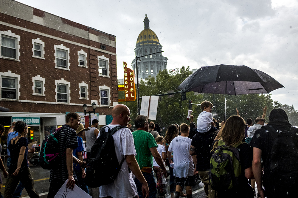 Rain pours over the march. A rally in response to white supremacist protests in Charlottesville, VA, Aug. 13, 2017. (Kevin J. Beaty/Denverite)  protest; charlottesville; rally; denver; colorado; kevinjbeaty; denverite; colfax