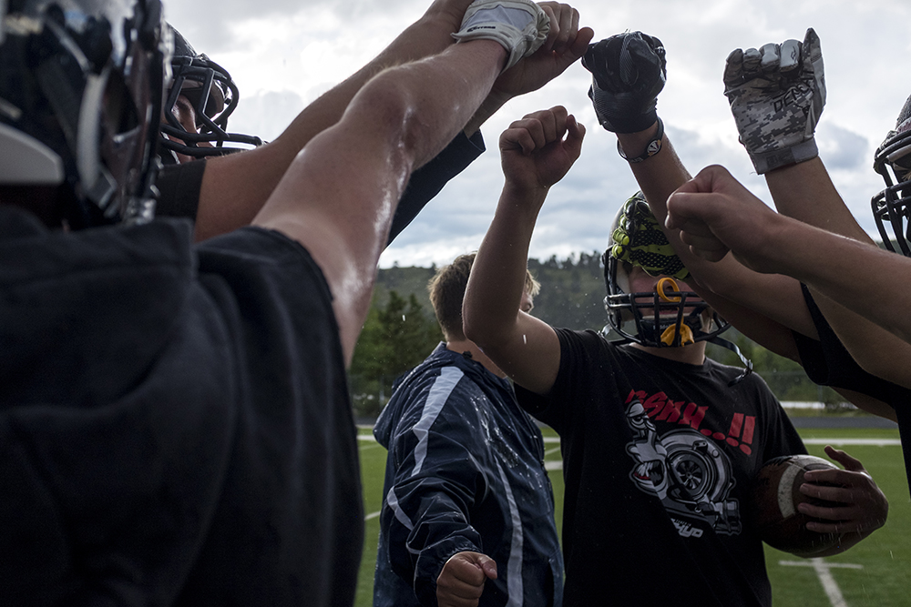 The Nederland Middle-High School varsity football team puts their hands together during practice, Aug. 15, 2017. (Kevin J. Beaty/Denverite)  high school football; sports; nederland; Beth Buglione; Nederland Middle-High School;