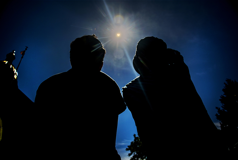 Basma (right) and Niama Al Nima gaze up at a solar eclipse over the Capitol, Aug. 21, 2017. (Kevin J. Beaty/Denverite)