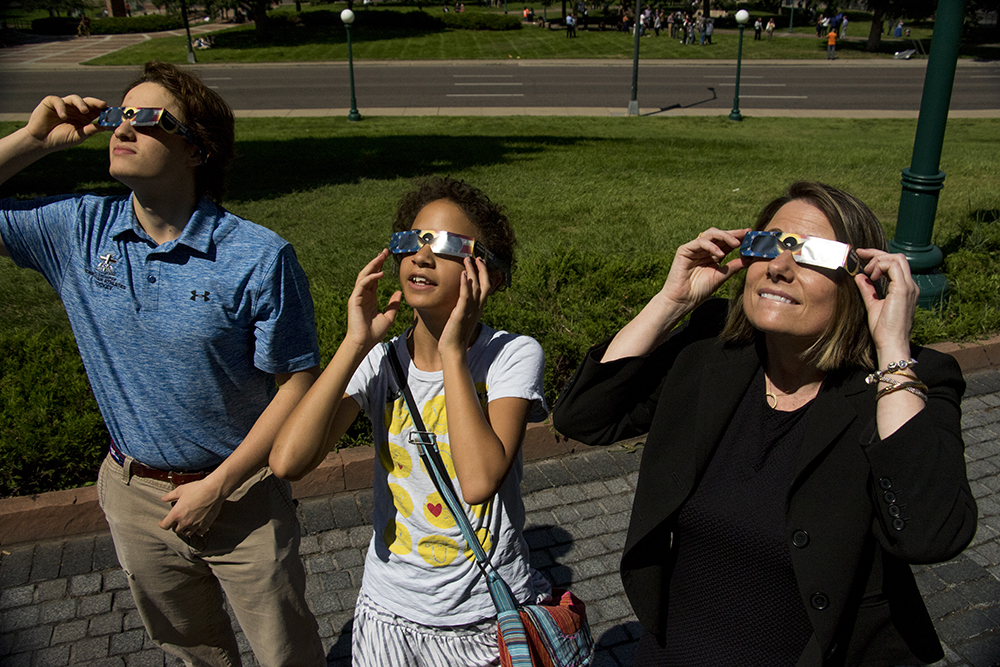 Priscilla (right to left), Willa and Sam Gartner gaze up at a solar eclipse over the Capitol, Aug. 21, 2017. (Kevin J. Beaty/Denverite)  solar eclipse; capitol hill; denver; colorado; the sun; kevinjbeaty; denverite;