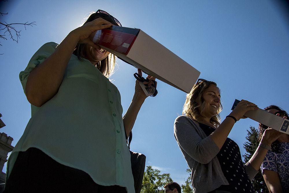Linnea Hulshof (left) and Shelby Schaefer watch a solar eclipse over the Capitol through home-made pinhole cameras, Aug. 21, 2017. (Kevin J. Beaty/Denverite)
