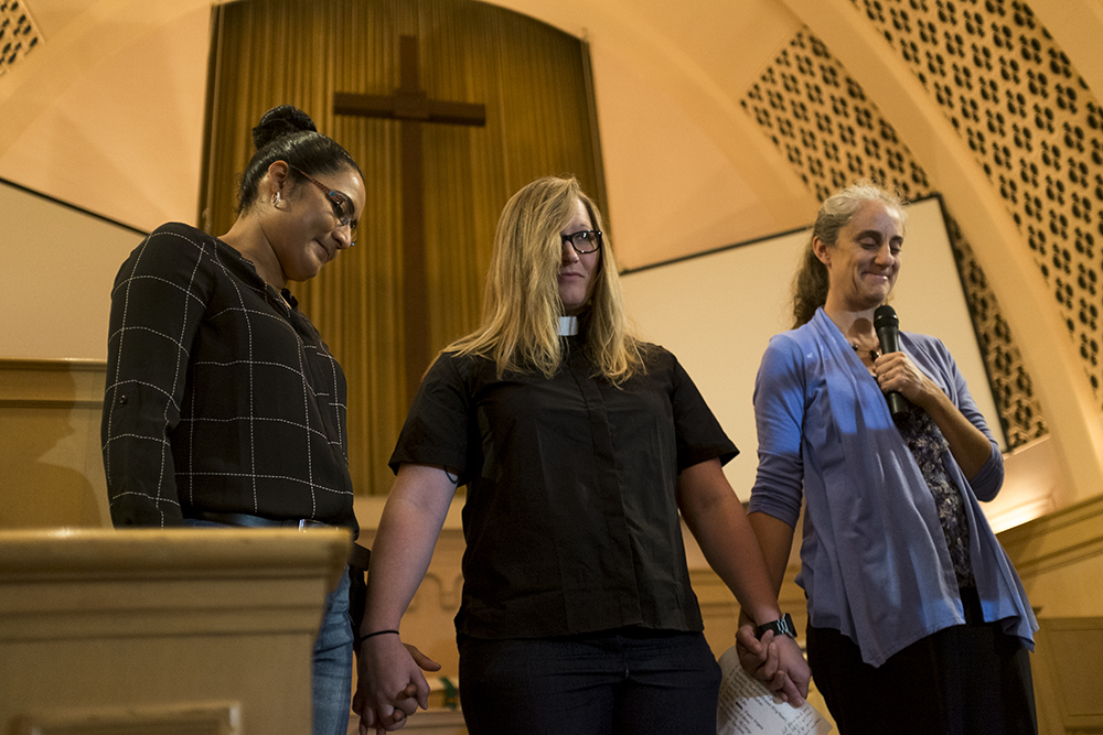 Araceli Velasquez (left) prays with Rev. Angie Heesacker and Jennifer Piper as she is welcomed into sanctuary by the Park Hill United Methodist Church and Temple Micah Synagogue congregations. Aug. 23, 2017. (Kevin J. Beaty/Denverite)