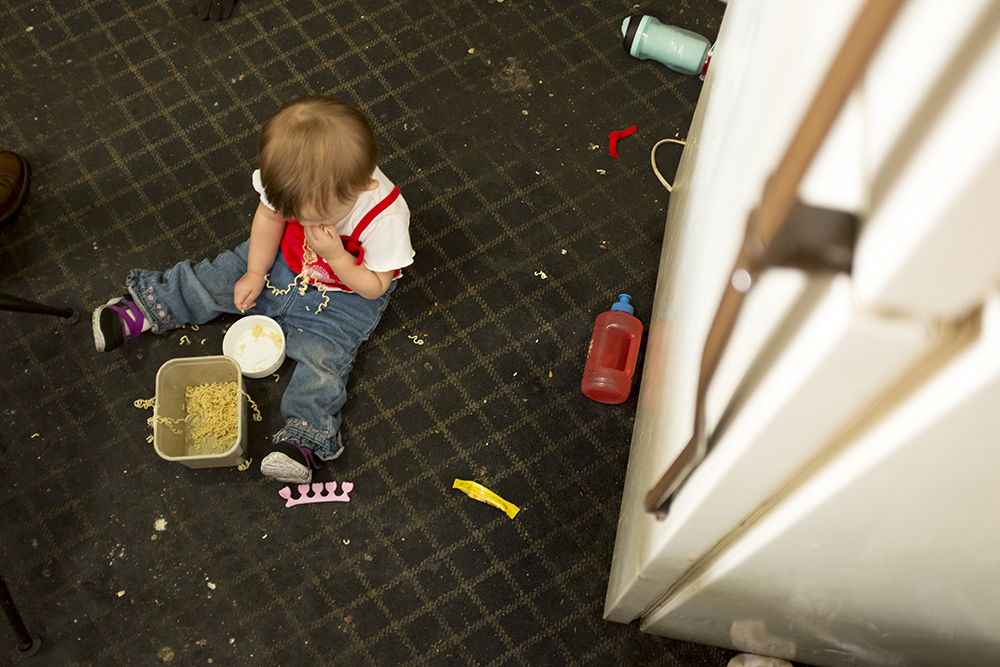 Ashley Angel's daughter, Saydia, eats on the floor inside the Carriage Motor Inn where they've been living for two and a half months, Sept. 27, 2017. (Kevin J. Beaty/Denverite)  denver; colorado; denverite; kevinjbeaty; motel; colfax; affordable housing;
