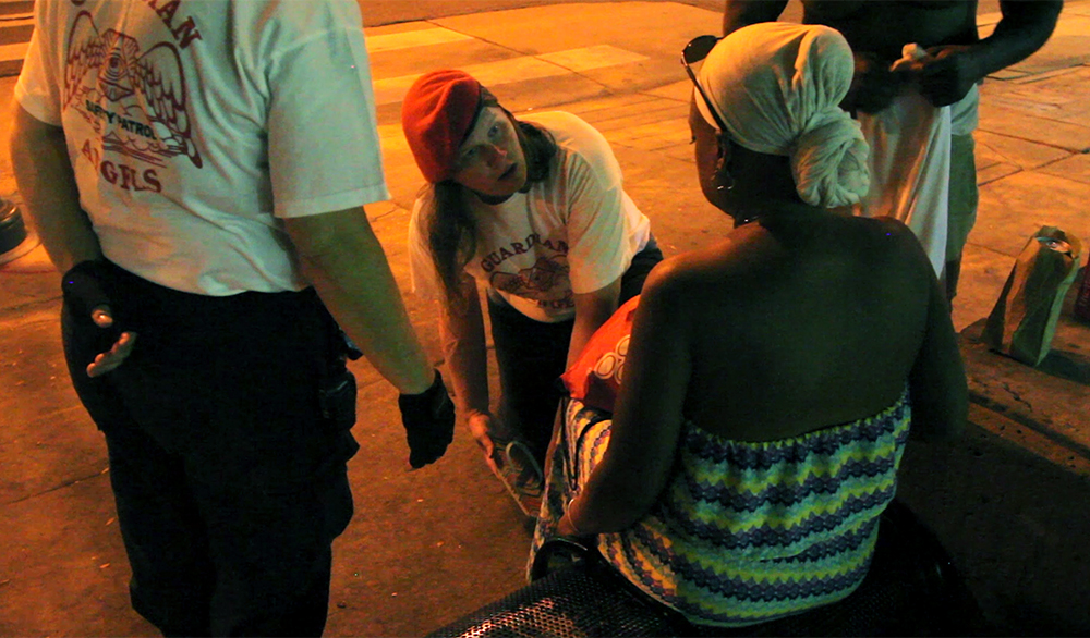 """Guardian Angel Corazon """"Valkyrie"""" Sierra tends to a woman who was punched during a street fight on East Colfax Avenue, Sept. 4, 2017. (Kevin J. Beaty)  denver; colorado; colfax; denverite; kevinjbeaty; guardian angels;"""