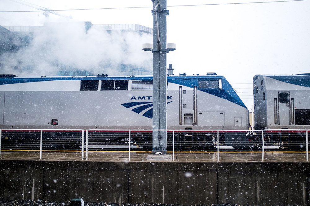 An Amtrak train at Union Station seen from inside the A Line on a snowy day, Oct. 9, 2017. (Kevin J. Beaty/Denverite)  snow; weather; cowx; denver; denverite; winter; kevinjbeaty; train; rtd; a line; colorado;