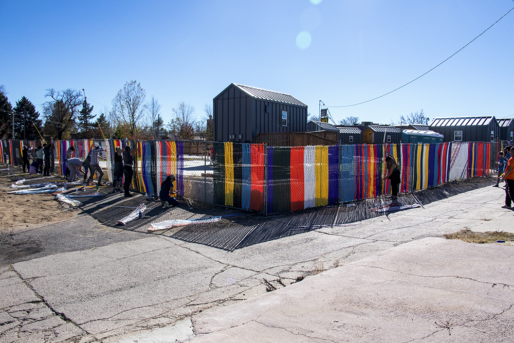 The Beloved Community Tiny Home Village gets some vibrant art on their fence, Oct. 29, 2017. (Kevin J. Beaty/Denverite)  tiny homes; beloved community tiny home village; rino; five points; homeless; right to rest; kevinjbeaty; denver; denverite; colorado;