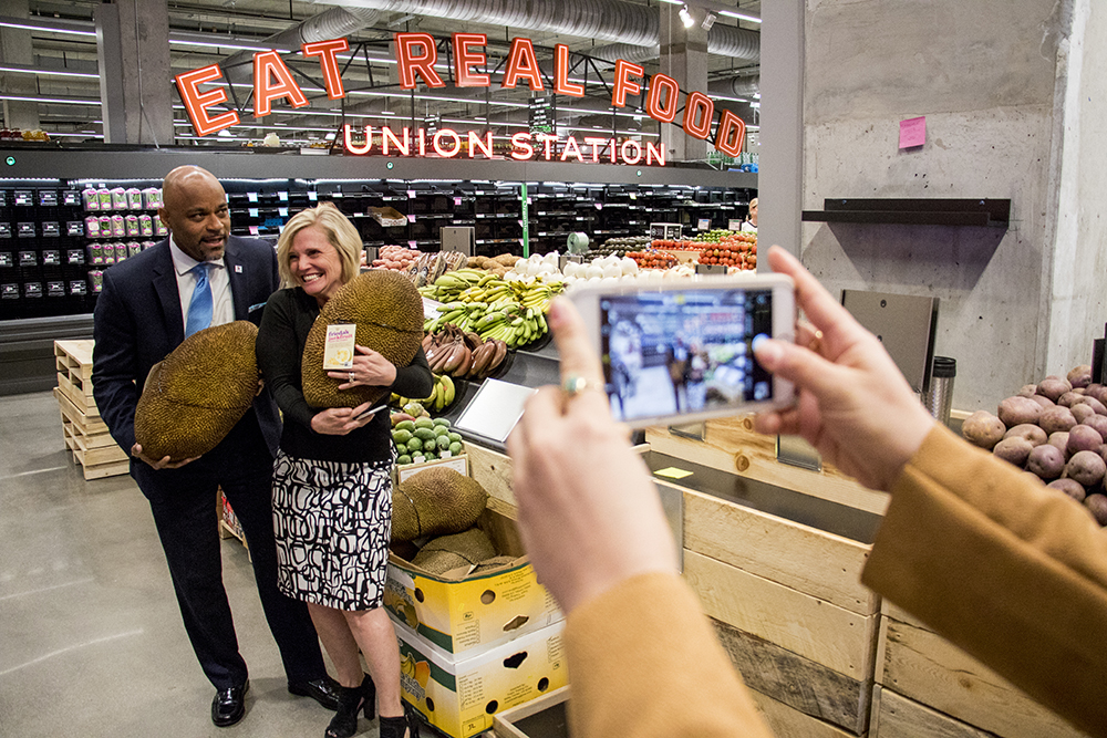 Mayor Michael Hancock and Downtown Denver Partnership President and CEO Tami Door hold some giant jackfruit. Whole Foods Market near Union Station is nearly ready to open, Nov. 13, 2017. (Kevin J. Beaty/Denverite)  whole foods; grocery store; union station; denver; denverite; kevinjbeaty; colorado; mayor michael hancock;