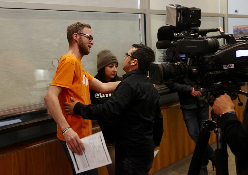 Bobby Reginelli, marketing director of Euflora, comforts an employee who didn't wish to be named after being beaten to the 4/20 permit. (Andrew Kenney/Denverite)
