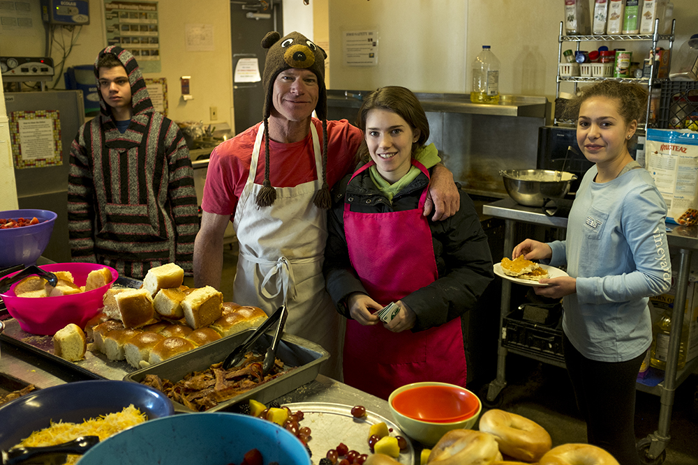 Volunteers Isaac and Farrah Bendell (far left and right) and Leah and Gregg Schuman make breakfast on Christmas morning as they've done for years. Urban Peak, a shelter for Denver's homeless youth, Dec. 25, 2017. (Kevin J. Beaty/Denverite)  homeless; urban peak; denver; denverite; colorado; kevinjbeaty;