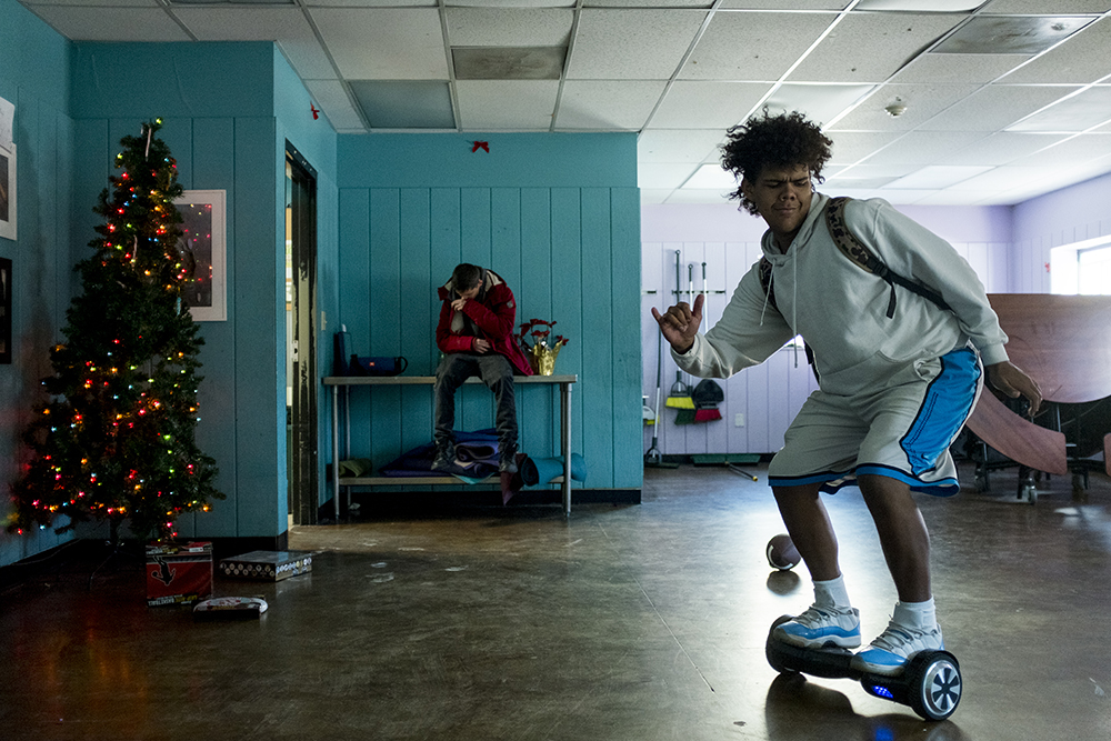 """Garret, who's 18 and has only been here for two weeks, dances on a """"hoverboard."""" Christmas Day at Urban Peak, a shelter for Denver's homeless youth, Dec. 25, 2017. (Kevin J. Beaty/Denverite)  homeless; urban peak; denver; denverite; colorado; kevinjbeaty;"""