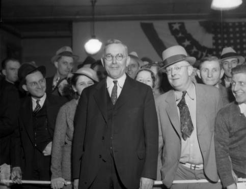 Denver Mayor Benjamin Franklin Stapleton (1873-1950) poses (eyeglasses and spotted tie), with a crowd of men and women, in Denver, Colorado; bunting is on the wall. Possibly campaign headquarters. (Harry Mellon Rhoads/Denver Public Library Western History and Genealogy Collection/Rh-1310)