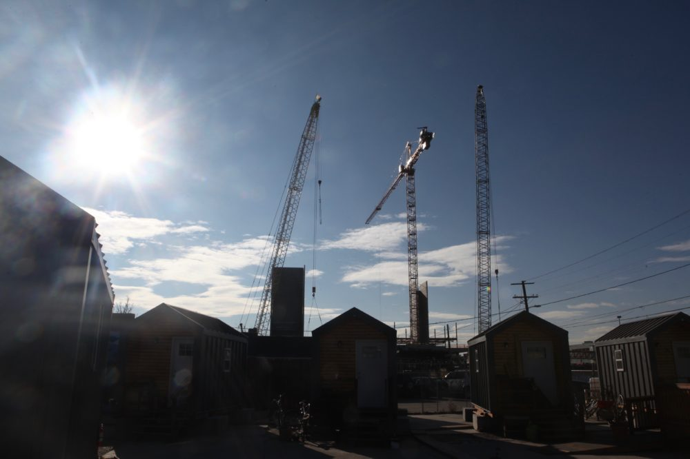 "The ""tiny homes"" of the Beloved Community Village beneath towering construction cranes in River North. (Andrew Kenney/Denverite)"