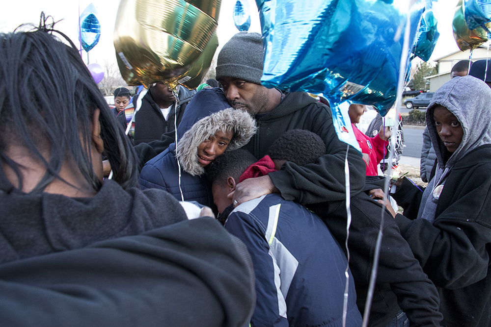 "Byron's siblings huddle together crying. One could hear, ""My brother is gone!"" A vigil for Byron Ware, who was shot and killed just days prior. Feb. 6, 2018. (Kevin J. Beaty/Denverite)  montbello; crime; gun violence; denver; denverite; kevinjbeaty; colorado; vigil;"