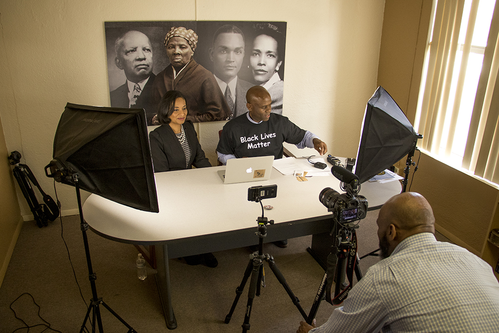 "Brother Jeff Fard (center), Lisa Calderón (left) and Ken Drew film and live stream ""30 Minutes With Brother Jeff"" in Fard's Welton Street office, March 15, 2018. (Kevin J. Beaty/Denverite)  denver; denverite; kevinjbeaty; colorado; five points; welton street;"
