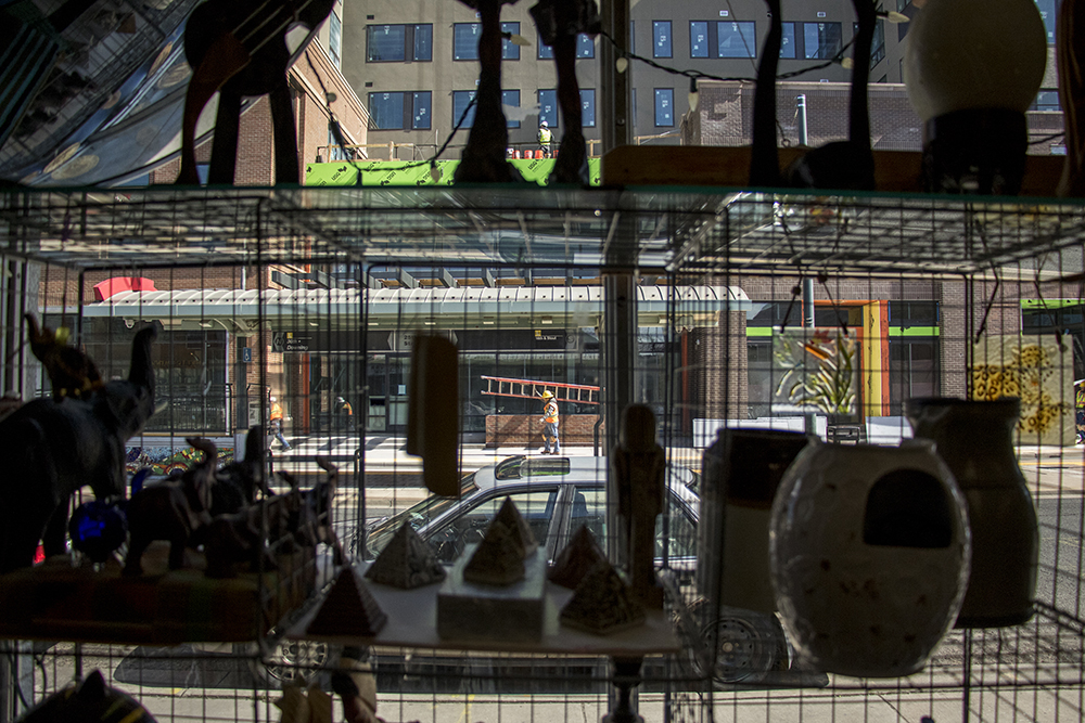 Construction workers seen from inside Neat Stuff At The Black Market on Welton Street, April 9, 2018. (Kevin J. Beaty/Denverite)  welton street; five points; denver; colorado; denverite; kevinjbeaty;