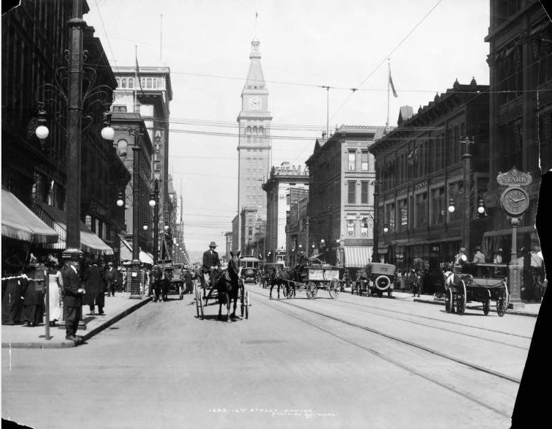 "View of 16th (Sixteenth) Street in Denver, Colorado; shows pedestrians, traffic, automobiles, a streetcar, and horse drawn buggies and wagons. Street lights, a clock and the Daniels & Fisher Tower line the sidewalks; signs read: ""Starr"" and ""Gano Downs."" (Denver Public Library/History Colorado Collection/CHS.X5354)"