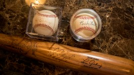 The last baseball bat signed by Lou Gehrig and balls signed by Gehrig and Babe Ruth. Marshall Fogle in his home, a shrine to baseball memorabilia, May 17, 2018. (Kevin J. Beaty/Denverite)  denver; colorado; denverite; baseball; sports; collecting; collector; kevinjbeaty;