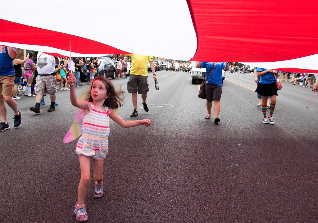 Eve, 4, skips beneath an enormous flag that leads the Denver PrideFest parade down Colfax Avenue, June 17, 2018. (Kevin J. Beaty/Denverite)