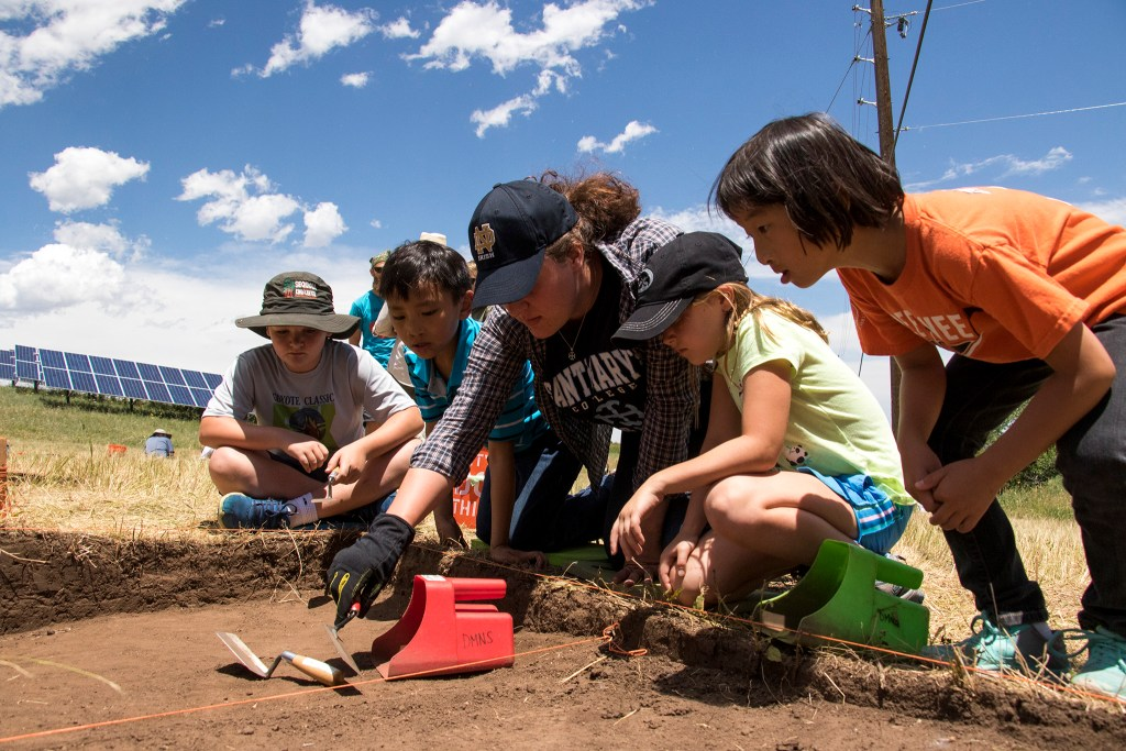 Denver Museum of Nature and Science volunteer Brianna Dalessandro (with the hat) shows Gavin Budden (from left), Andrew Waskosky, Evelyn Budden and Amanda Waskosky how to excavate for artifacts at Magic Mountain, an archaeological dig site in Golden, June 22, 2018. (Kevin J. Beaty/Denverite)