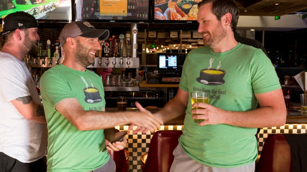 Chris Lombardi (left) and Rob Toftness shake hands after winning, sort of, the Cherry Cricket's chile cookoff, July 19, 2018. (Kevin J. Beaty/Denverite)