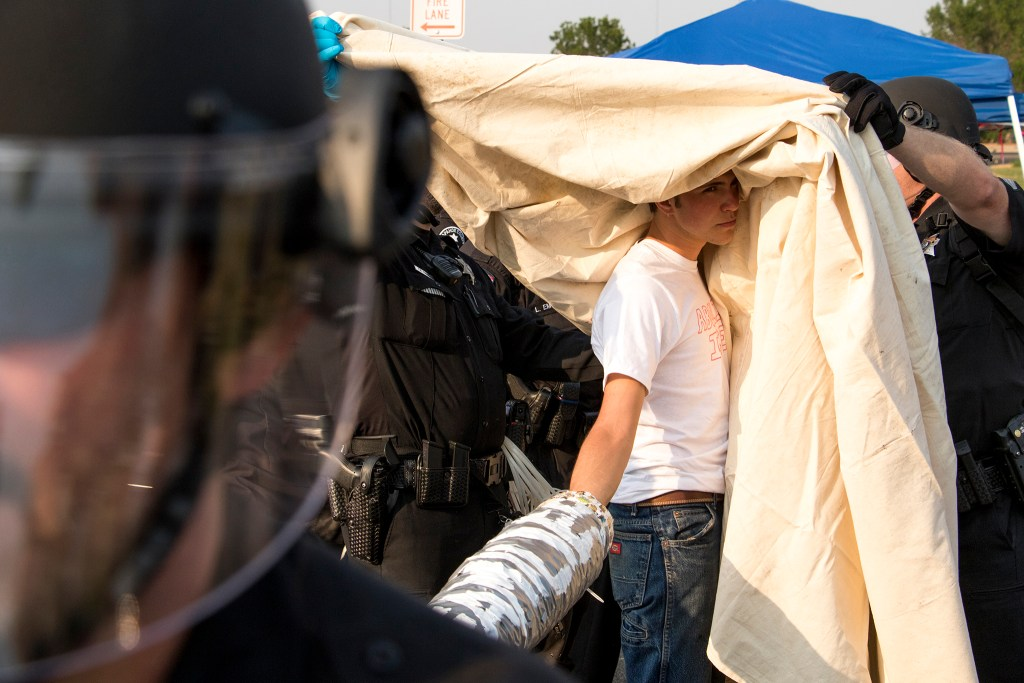 An activist named Jamie is covered with canvas before police attempt to cut off equipment used to blockade the local headquarters for U.S. Immigrations and Customs Enforcement in Centennial, Aug. 2, 2018. (Kevin J. Beaty/Denverite)