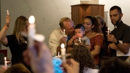 Araceli Velasquez and Rabbi Adam Morris kiss her youngest son, Kevin, as they commemorate one year since she entered sanctuary here in the shared home of Temple Micah synagogue and Park Hill United Methodist Church. Velasquez has been fighting to avoid a deportation order for more than seven years. Aug. 9, 2018. (Kevin J. Beaty/Denverite)