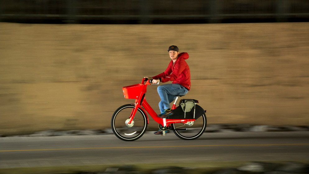 A man in a red hoodie rides a red Jump bike on the Cherry Creek Trail, Aug. 20, 2018. (Kevin J. Beaty/Denverite)