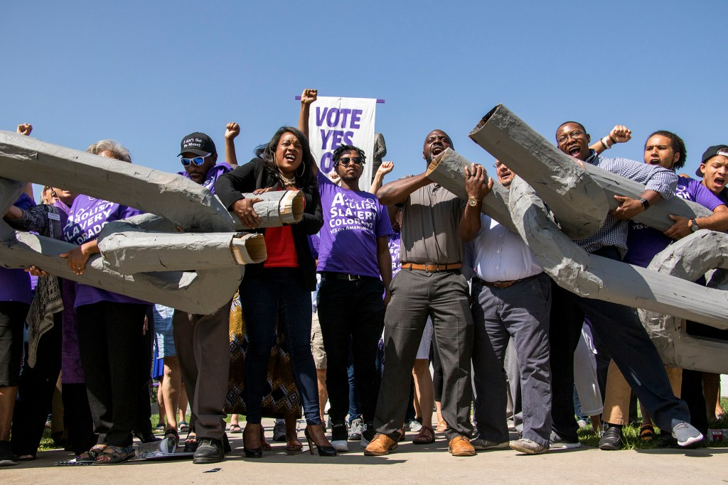"Activists break the chains of a giant pair of shackles after a rally to vote ""yes"" on Amendment A, to make slavery unconstitutional in Colorado, at City Park, Aug. 28, 2018. (Kevin J. Beaty/Denverite)"