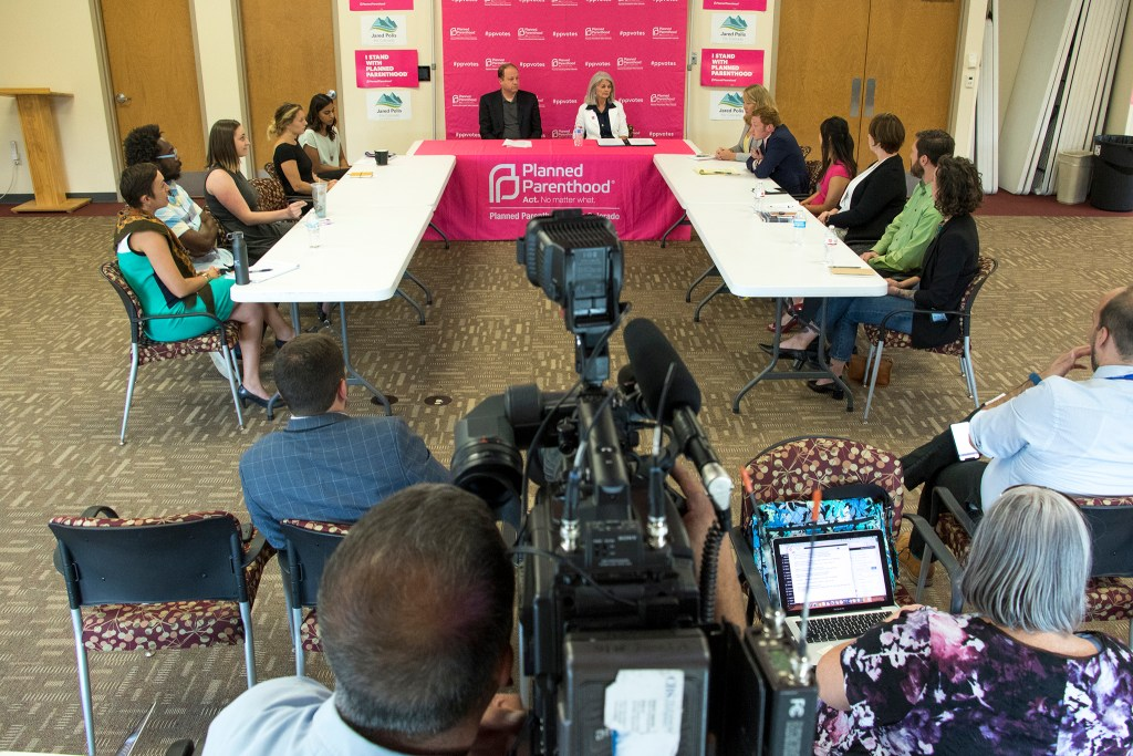 Democratic gubernatorial candidate Jared Polis sits next to Vicki Cowart, president and CEO of Planned Parenthood of the Rocky Mountans, during a round table discussion and press conference, at the organization's headquarters in Northeast Park Hill, Aug. 30, 2018. (Kevin J. Beaty/Denverite)