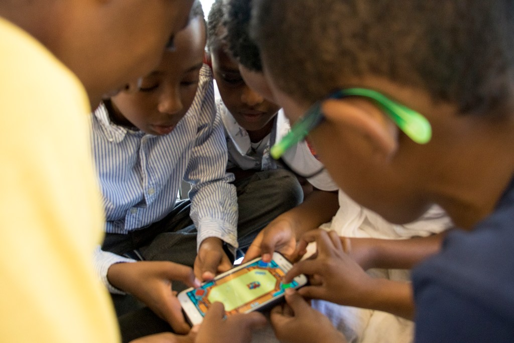 Kids play a mobile game during Ethiopian New Year services at St. Mary Ethiopan Orthodox Church in Aurora, Sept. 9, 2018. (Kevin J. Beaty/Denverite)