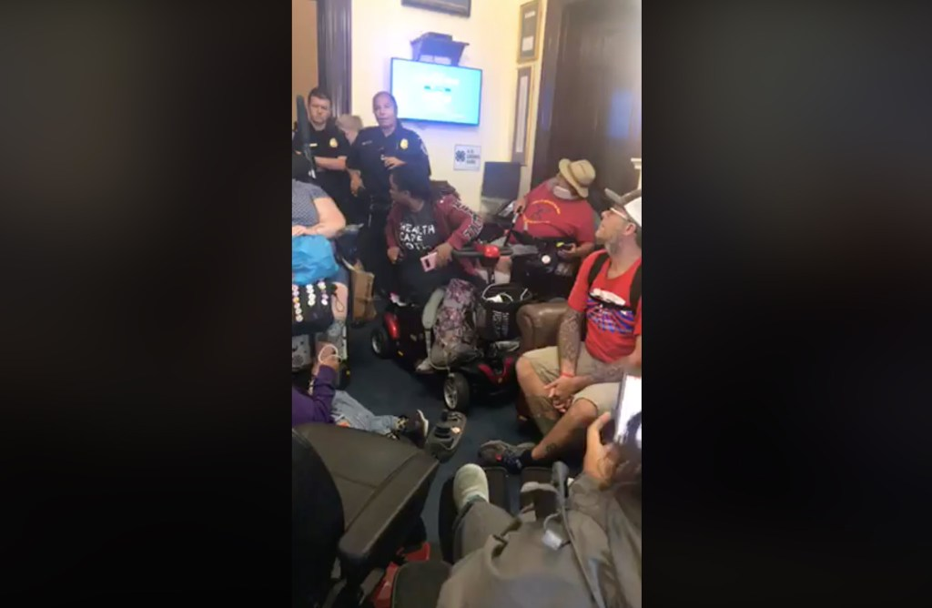 Police speak to ADAPT protesters holed up in Sen. Cory Gardner's office in Washington, D.C. Sept. 20, 2018. (Hope Russell Moseley's live Facebook stream)