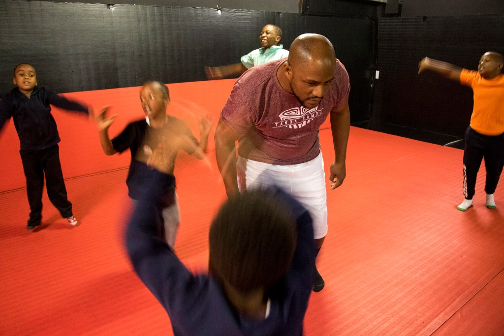 Coach Lumumba Sayers talks tough to kids doing jumping jacks during boxing class at Heavy Hearts Heavy Hands gym in Aurora, Oct. 17, 2018. (Kevin J. Beaty/Denverite)