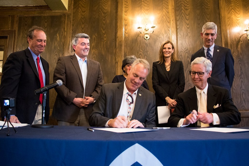 Secretary of the Interior Ryan Zinke puts ink to paper at a press conference with Rep. Ed Perlmutter and Sen. Cory Gardner to announce a new partnership between the Colorado School of Mines and U.S. Geological Survey. Denver Athletic Club, Oct. 22, 2018. (Kevin J. Beaty/Denverite)