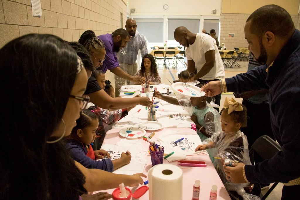 Kids paint t-shirts with their parents during A Father Daughter Occasion at the Dahlia Campus for Health and Well-Being in Northeast Park Hill, Oct. 27, 2018. (Kevin J. Beaty/Denverite)