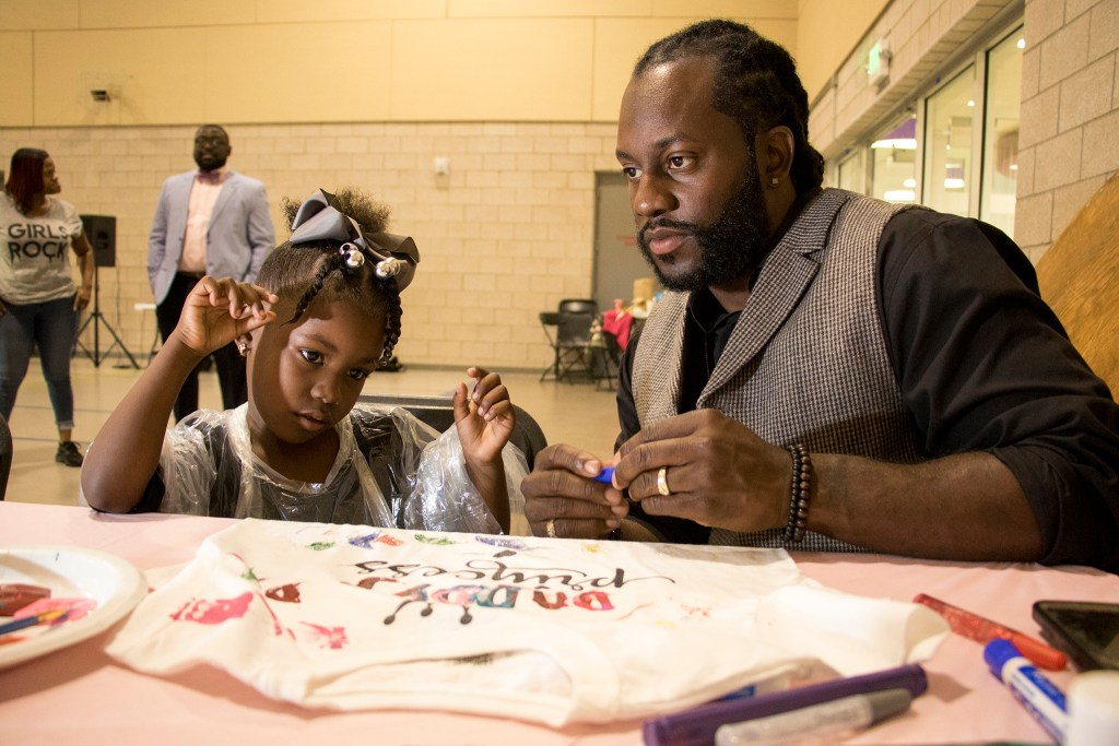 DJ Ktone and his daughter, Kourtney (4) paint t-shirts. A Father Daughter Occasion at the Dahlia Campus for Health and Well-Being in Northeast Park Hill, Oct. 27, 2018. (Kevin J. Beaty/Denverite)