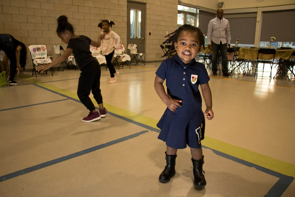 Ava (2) dances as her grandfather, Christopher Bishop, watches in the background. A Father Daughter Occasion at the Dahlia Campus for Health and Well-Being in Northeast Park Hill, Oct. 27, 2018. (Kevin J. Beaty/Denverite)