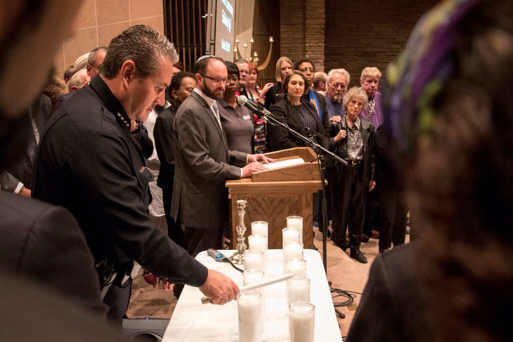 Denver Police Chief Paul Pazen lights a candle for a victim of a mass shooting at a Pittsburgh synagogue during a vigil at Temple Emanuel, Oct. 28, 2018. (Kevin J. Beaty/Denverite)