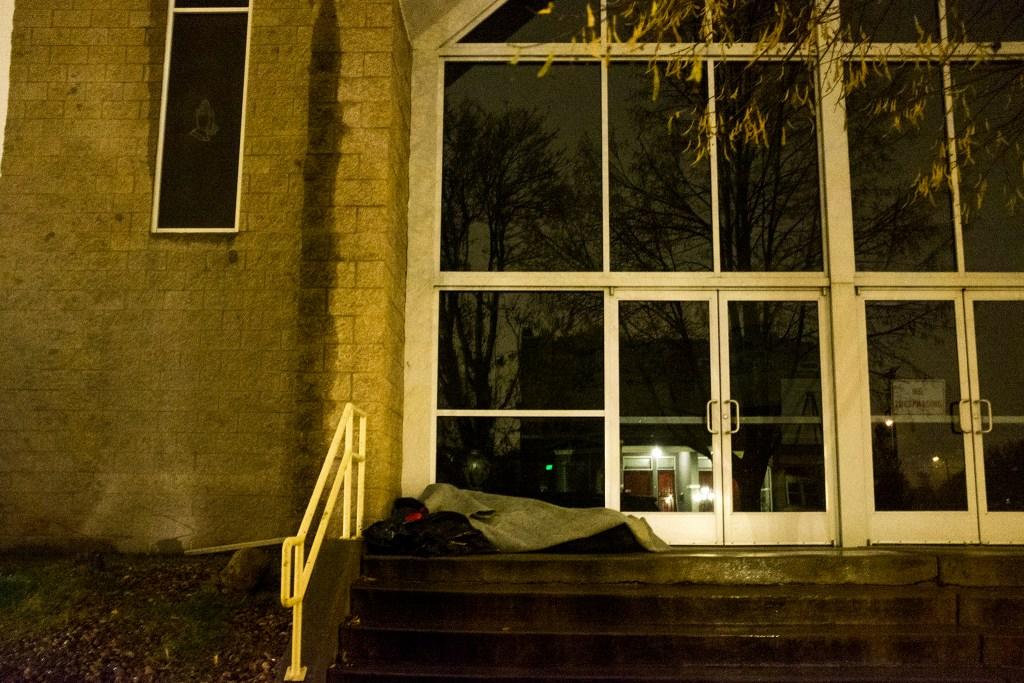 A man sleeps under a blanket in Five Points, Oct. 30, 2018. (Kevin J. Beaty/Denverite)