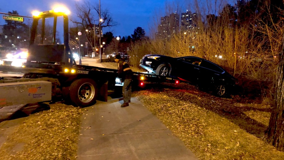 A tow truck driver pulls a wrecked vehicle off of a hill just above the Cherry Creek Trail. (David Sachs/Denverite)