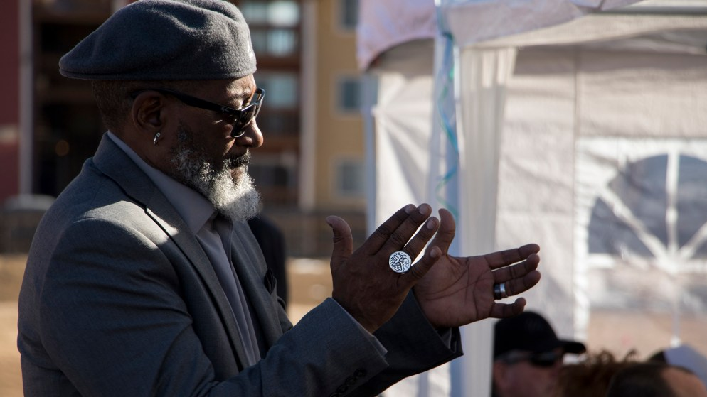 Hassan Latif, founder and executive director of Second Chance Center, applauses during groundbreaking for a new supportive housing project behind the Elevation Christian Church in Aurora, Jan. 4, 2018. (Kevin J. Beaty/Denverite)