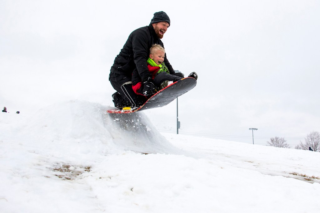 Johnny Borchaedt and his son Chase will fly over a sled jump in Ruby Hill on January 12, 2019.  (Kevin J. Beaty / Denverite)
