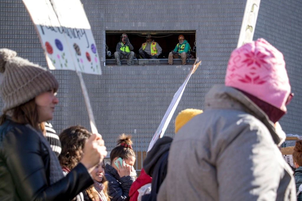 Construction workers inside the Denver Art Museum's north building watch the 2019 Womxn's March, Jan. 19, 2019. (Kevin J. Beaty/Denverite)
