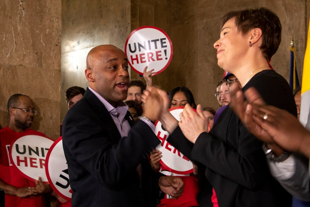 Mayor Michael Hancock locks hands with City Councilwoman Robin Kniech during a press conference on a city bill to increase minimum wage for city workers, Feb. 14, 2019. (Kevin J. Beaty/Denverite)